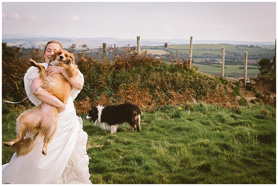 Wedding with Rescue Dogs - Bride cuddling one of her rescue dogs with another in the background by Wild Connections Photography