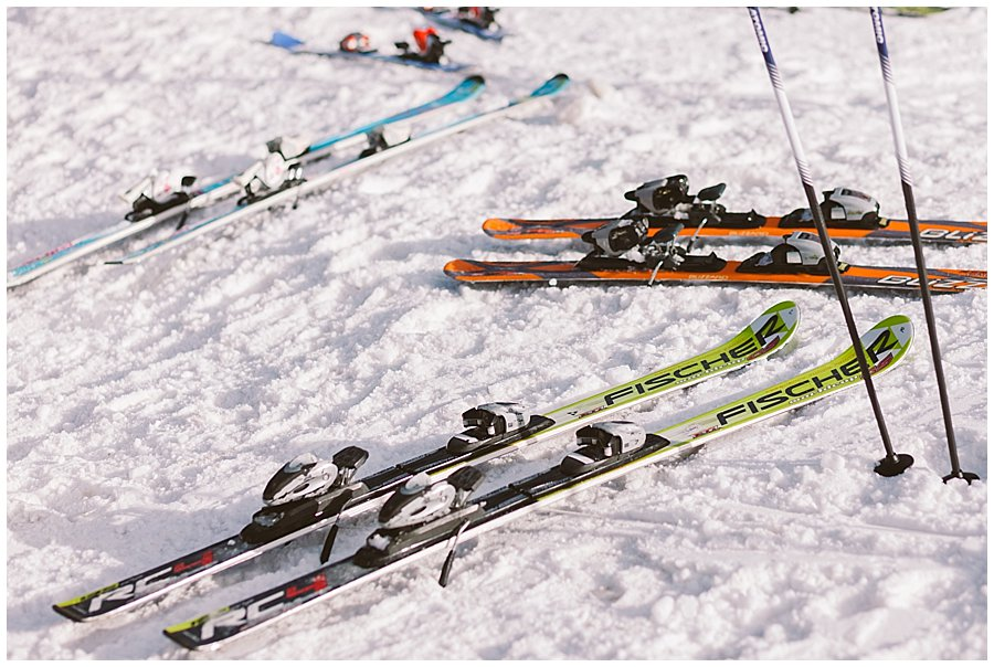 Skis lying on the floor in the snow at the bottom of a ski run