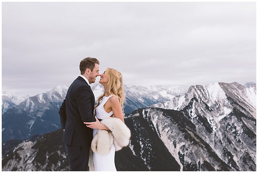 Image of a bride and groom standing nose to nose on a mountain top with snow-capped mountains in the background