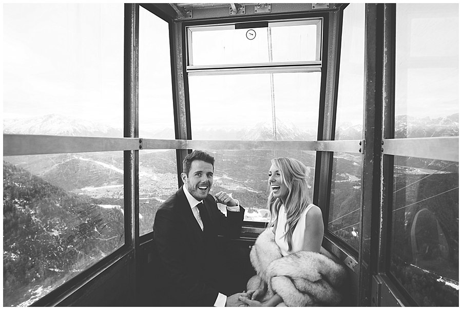 Bride and groom in a small mountain cable car laughing