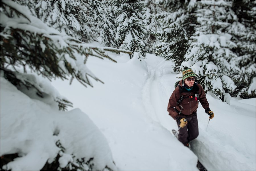 A male skier hikes through deep snow by Wild Connections Photography