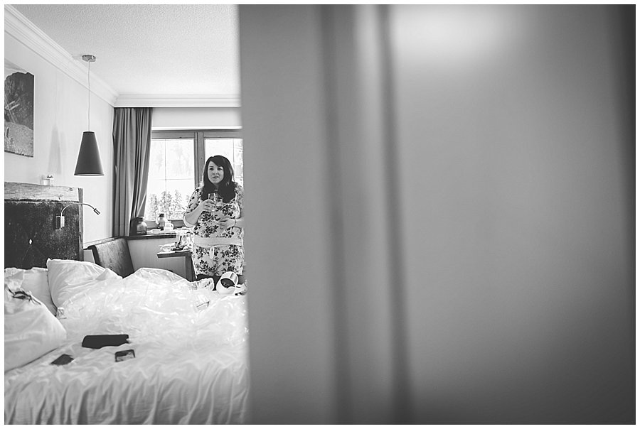 Bride Bec stands in floral tracksuit in hotel room drinking a glass of water