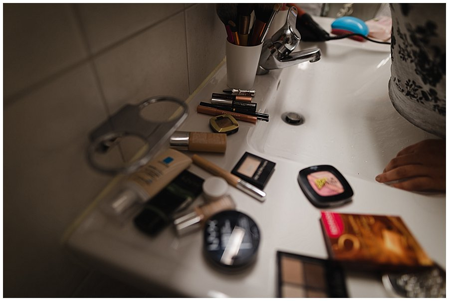 Assorted makeup products scattered around the bathroom sink