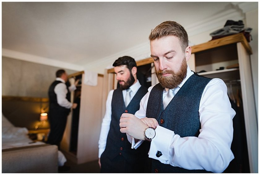 Groom prep groom gets ready in a hotel room putting on his watch by Wild Connections Photography
