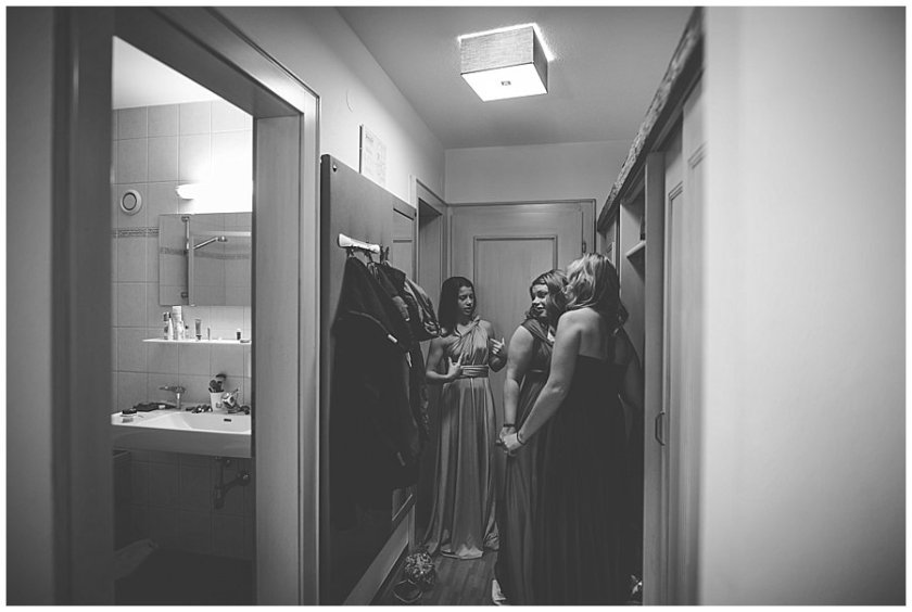 Bridesmaids admire their dresses in the mirror of the hotel room hallway