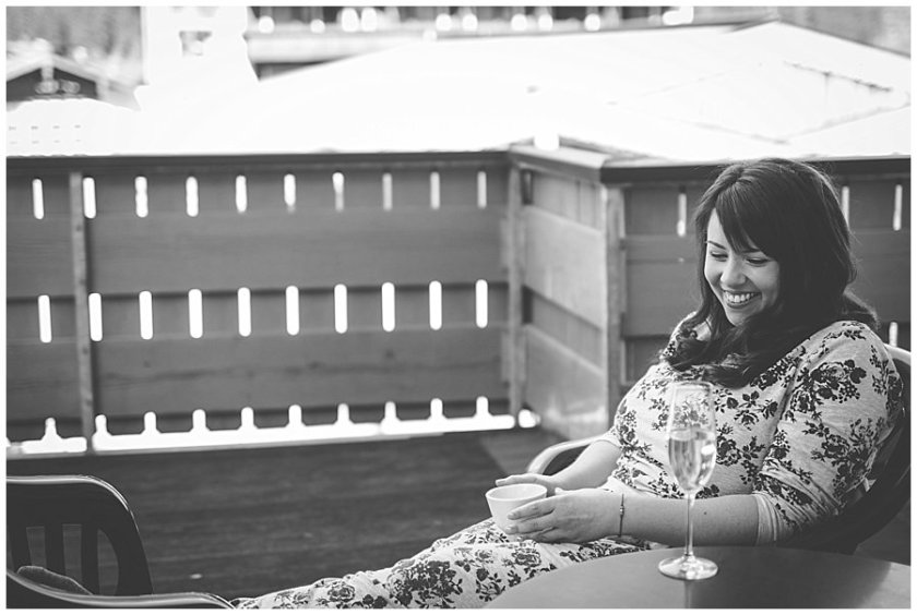 The bride Bec sitting on her balcony with a cup of tea and a glass of prosecco in a flower print tracksuit