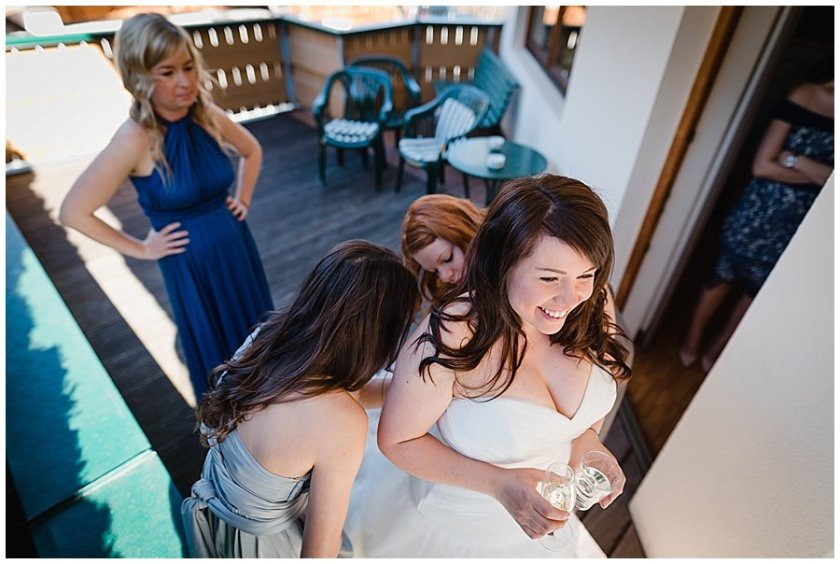The bridesmaids do up the buttons on Bec's wedding dress as she stands smiling holding a glass of water and a glass of prosecco