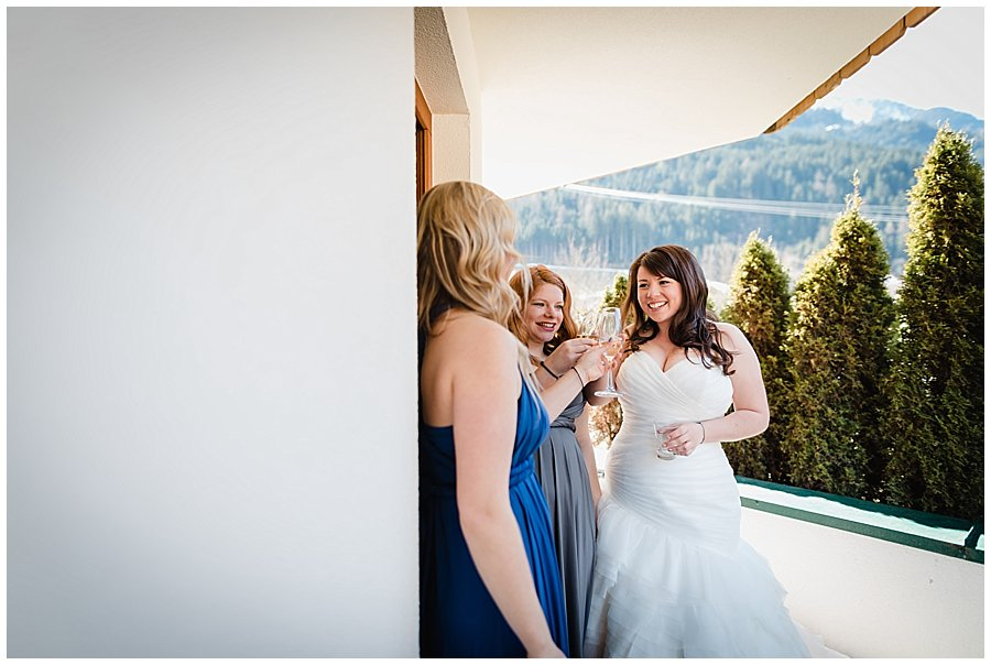 The bride and bridesmaids raise a glass of prosecco on the hotel balcony