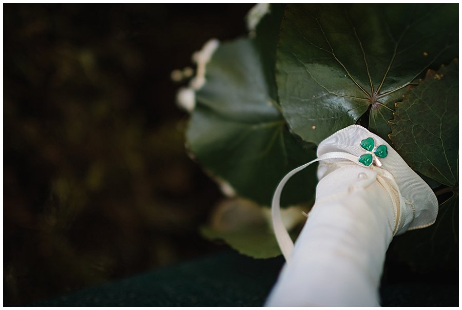 A clover pin on the bouquet for good luck and to celebrate St Patrick's day