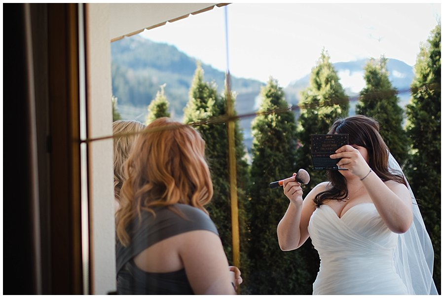 The bride powders her face in a compact mirror