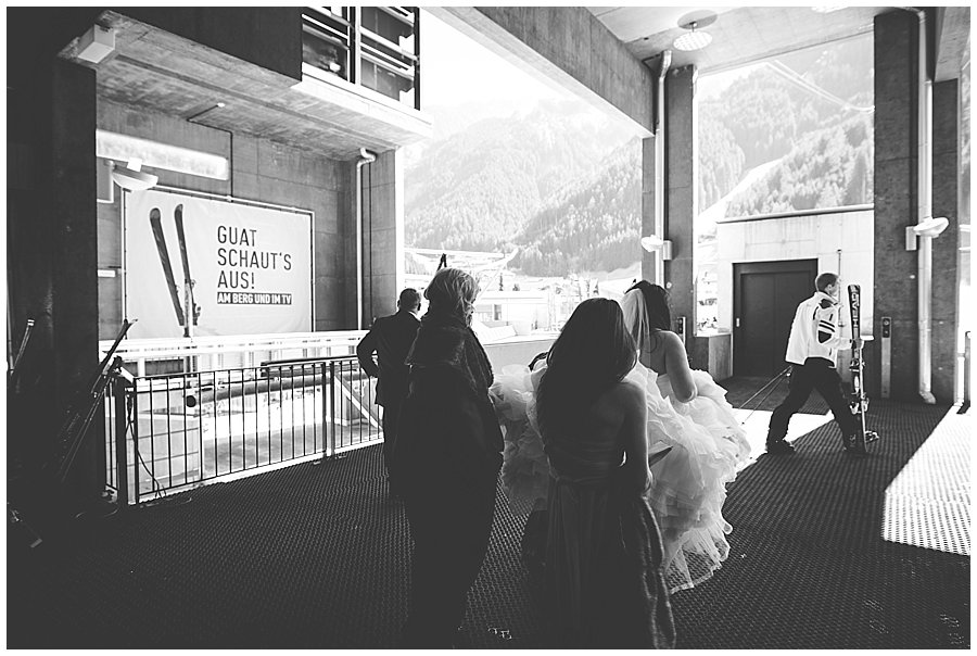 "Bride embarks on cable car with skiers and a sign in the background that say ""looking good"" in German"
