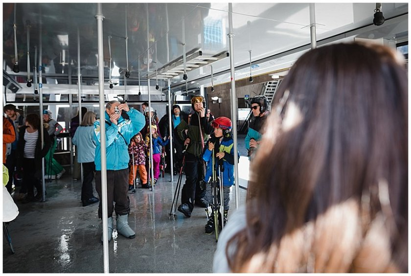 A skier in the cable car uses a disposable film camera to take a photograph of the bride