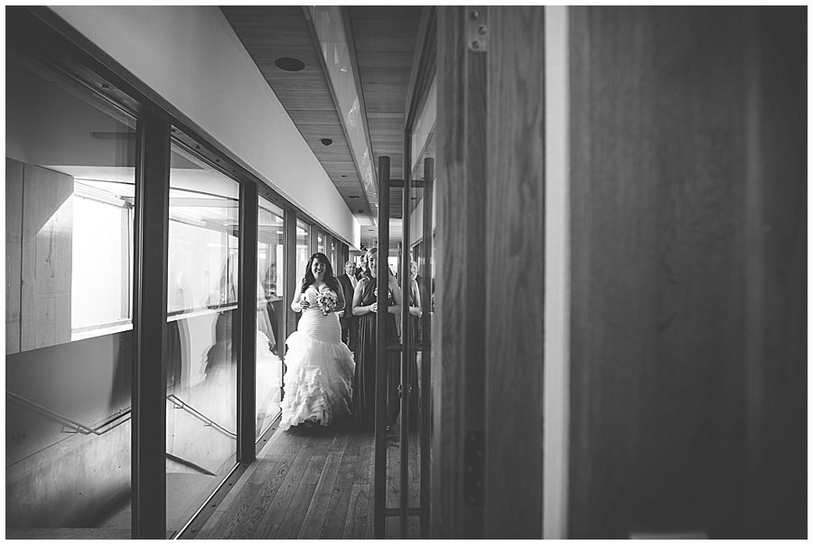 The bride walks down the corridor towards the ceremony room with her bridesmaids