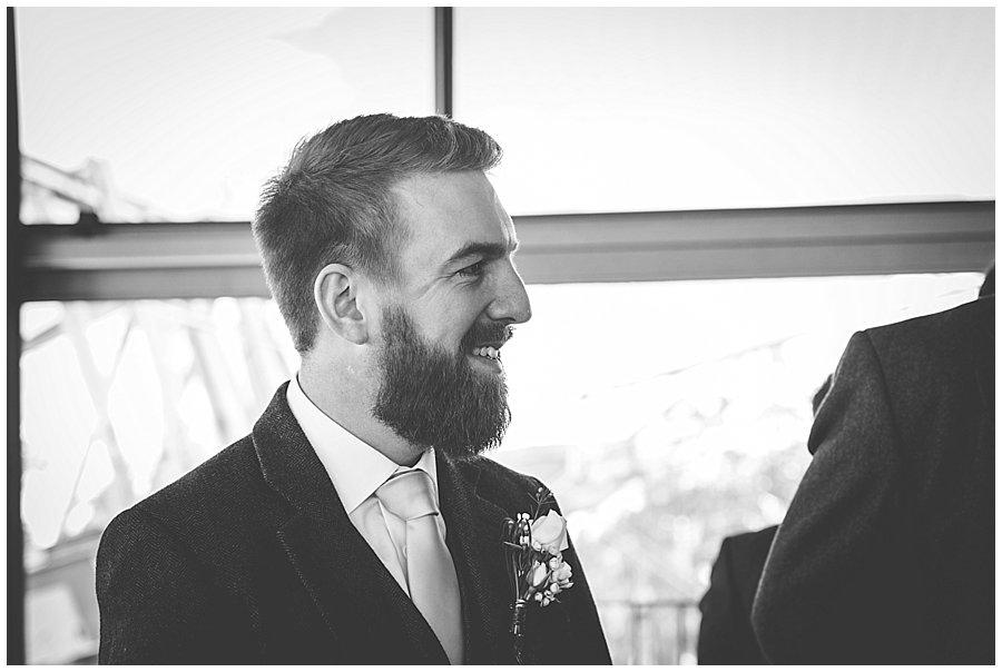 The groom Dan smiles as he sees his bride approaching