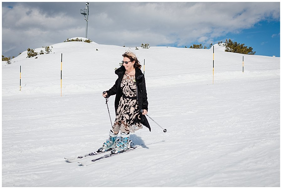 The mother of the bride skis in her wedding outfit