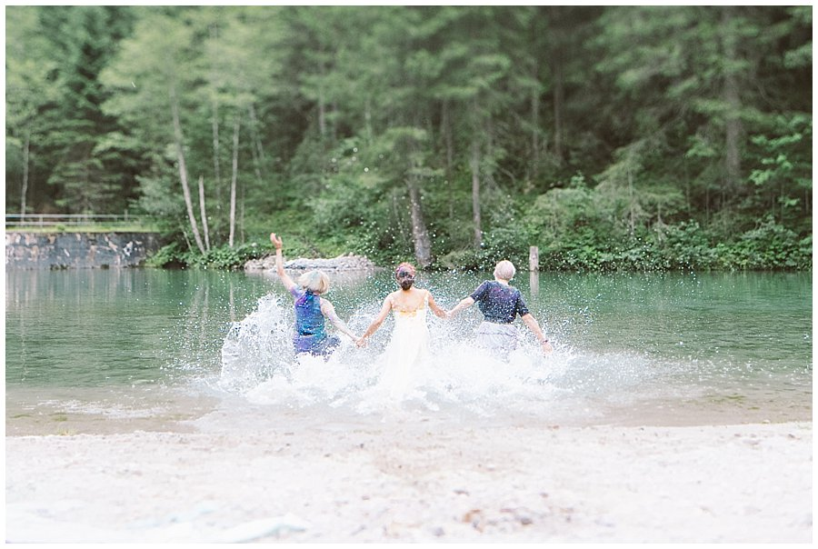 Trash The Dress Photo Shoot Austria - Bride and her sisters run into the lake fully clothed by Wild Connections Photography