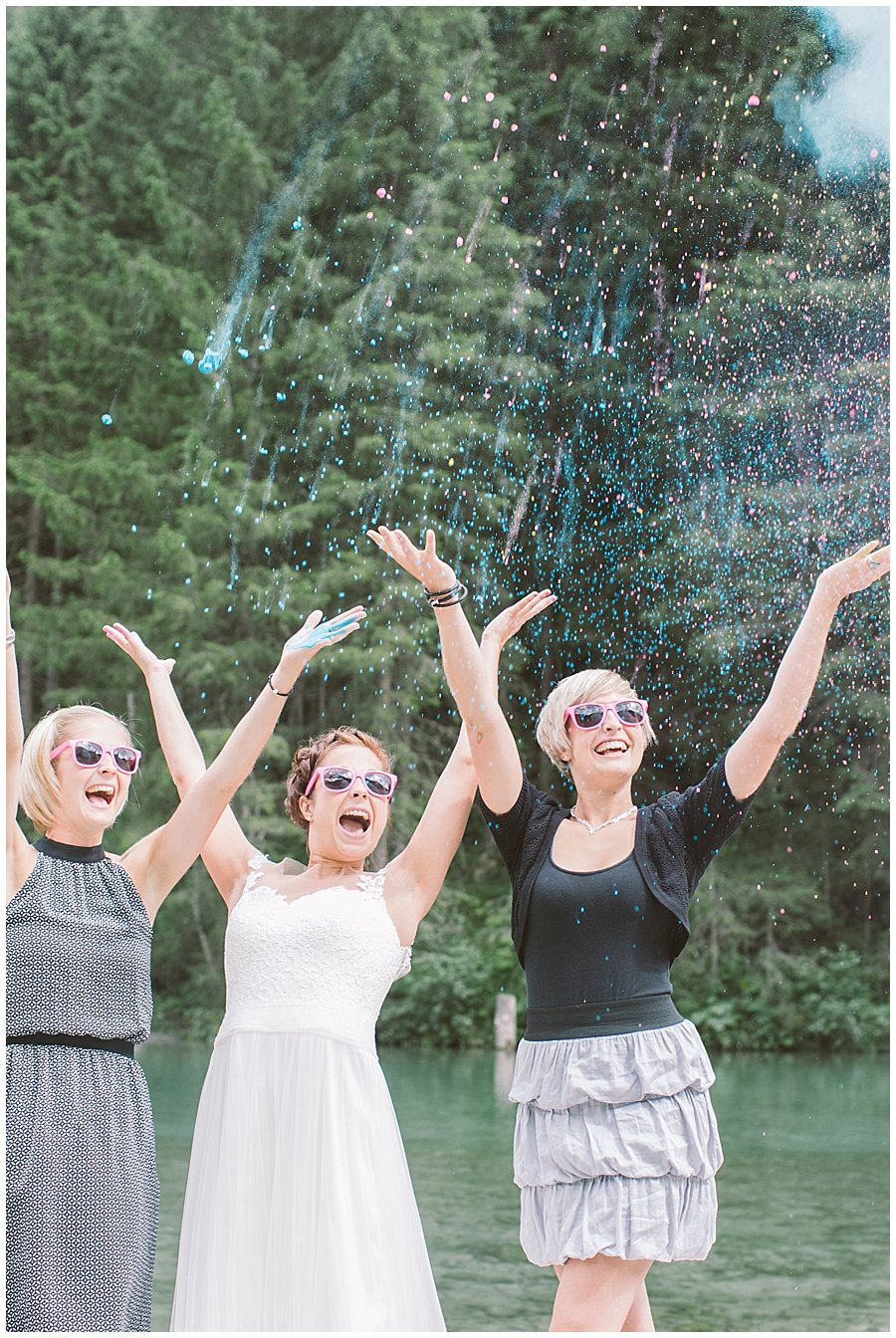 Trash The Dress Photo Shoot Austria - Bride and her sisters throw holi powder paint into the air by Wild Connections Photography