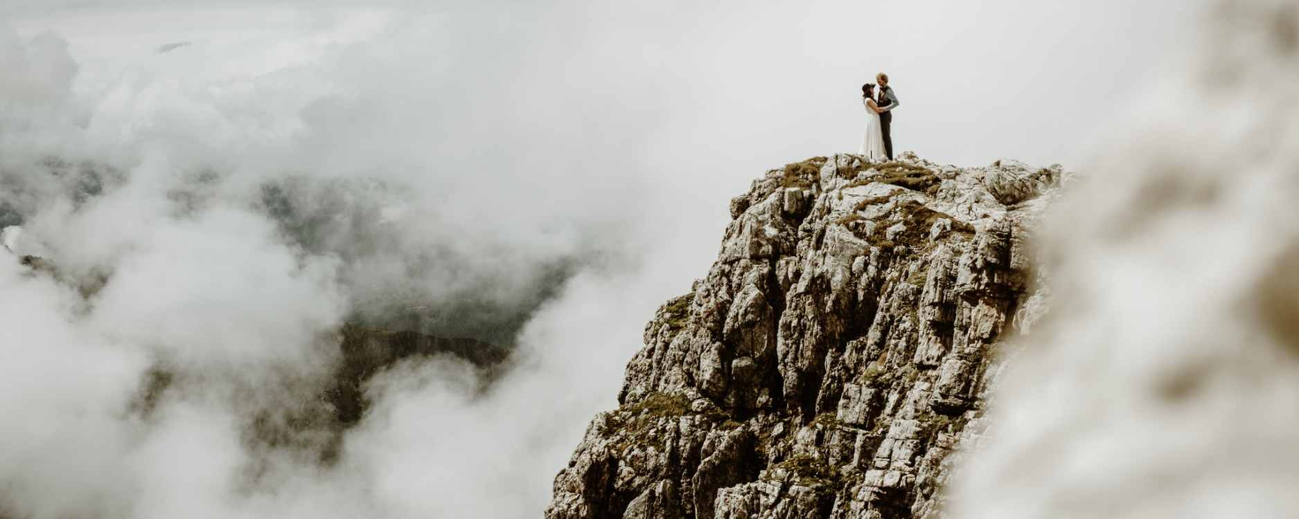 Dolomites elopement bride and groom on a huge cliff on the Pale di San Martino by Wild Connections Photography