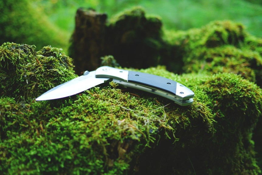 knife in nature grass moss - History Channel Alone Gear List