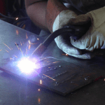 Arc welding using car batteries and quarters.