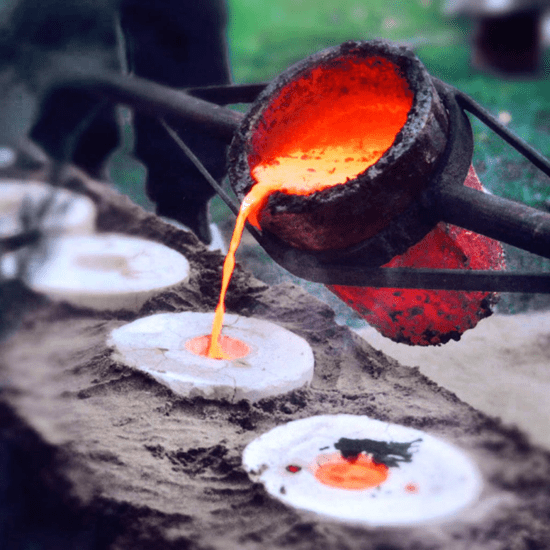 Pouring molten metal from crucible into sand molds