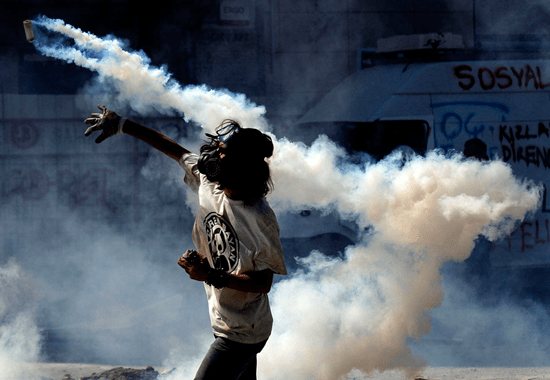 Civilian throwing a homemade tear gas bomb