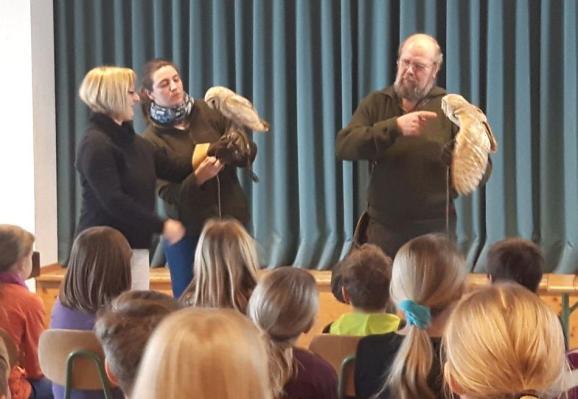 Jasmin und Gerhard Kopfhammer zeigen den Schülern die zahmen Schleiereulen.