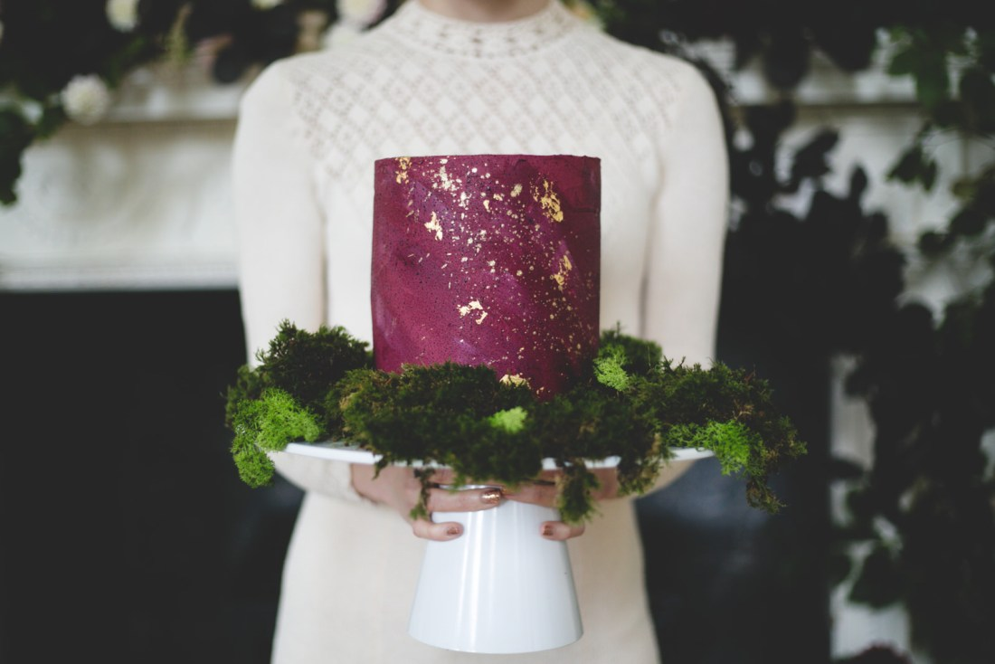 Burgundy and gold foil decorated wedding cake with moss decorations and stand