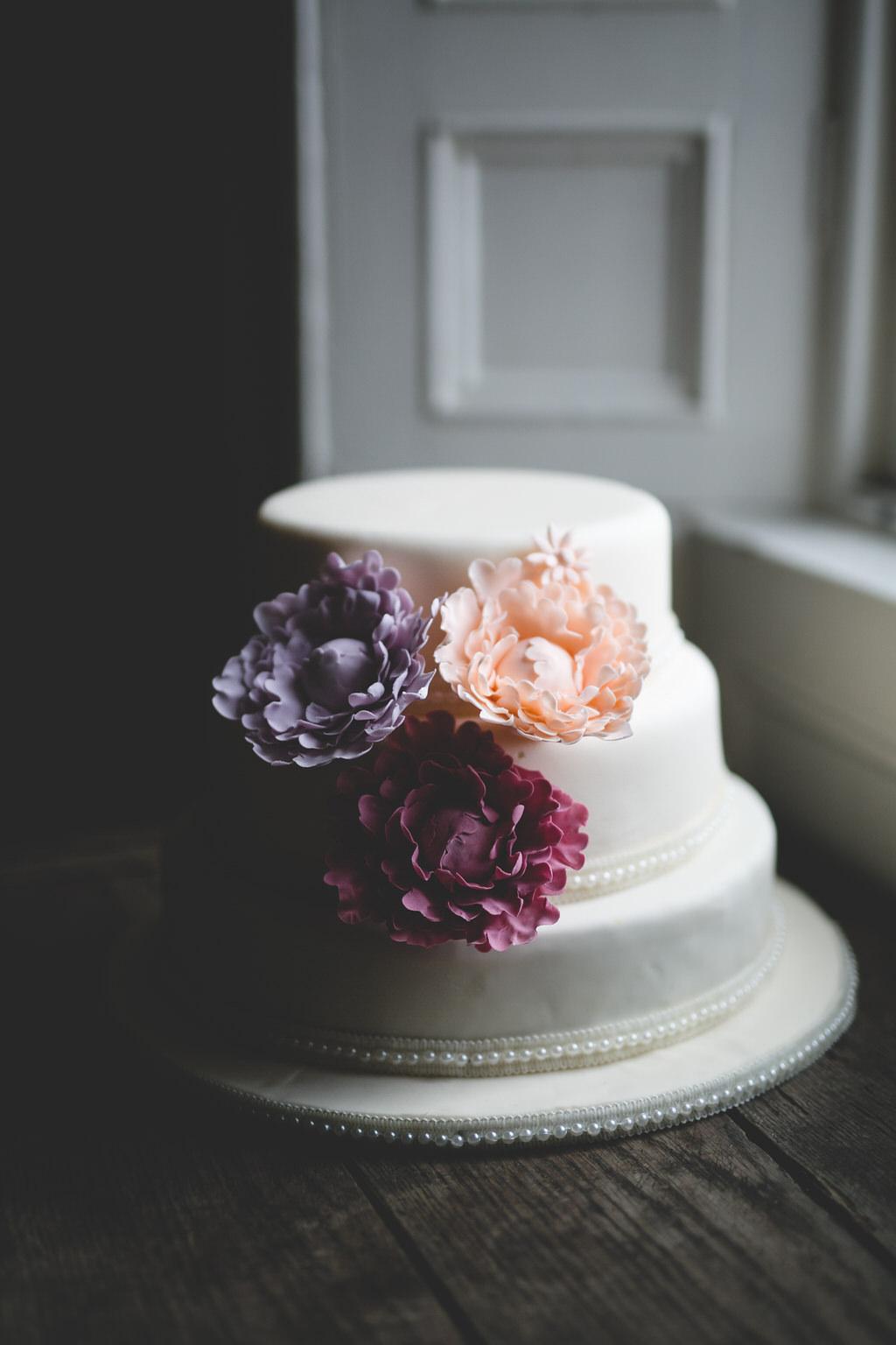 Simple, stylish & elegant wedding cake in white with iced flower decorations