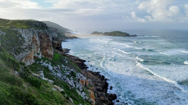 Waves clash with the rocks at Robberg Beach