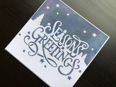 Hand made Christmas card with inked background and seasons greetings edger die