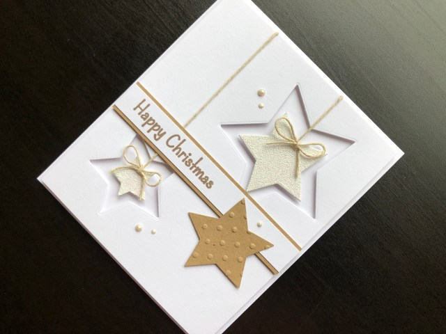 Hand made Christmas card with die cut stars and heat embossing.