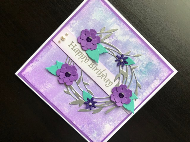 Hand made birthday card with inked background and die cut floral wreath