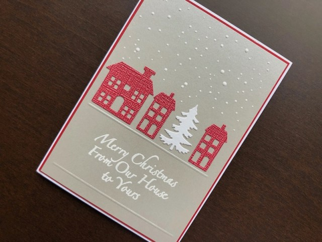 Hand made Christmas card with die cut houses, heat embossed snowfall and sentiment.