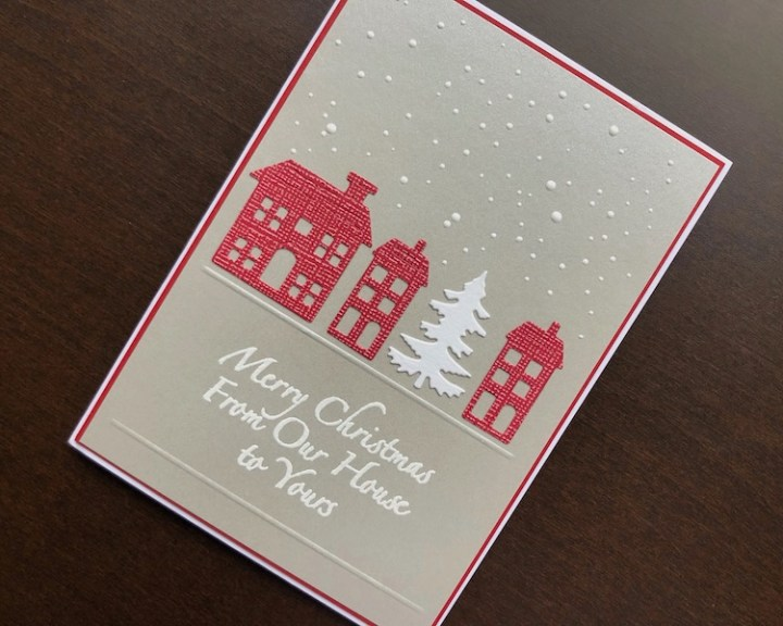 Hand made Christmas card with die cut houses and stamped and heat embossed sentiment