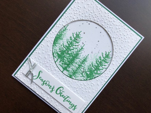 Hand made Christmas card with stamped pine trees, embossed snowfall and glitter snowfall.