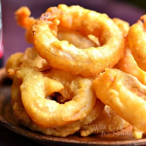 close up view of view from above of fried beer batter onion rings in a wood bowl on a wood table with bottle of killians in background