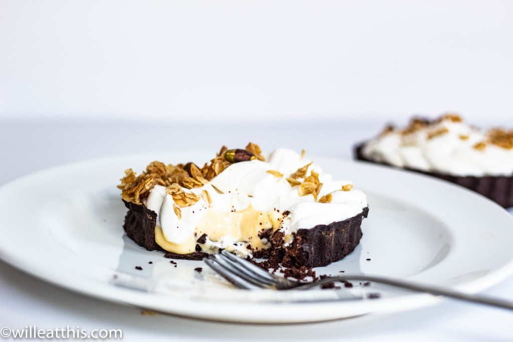 A blood orange curd tart in a chocolate crust topped with coconut yogurt and granola.