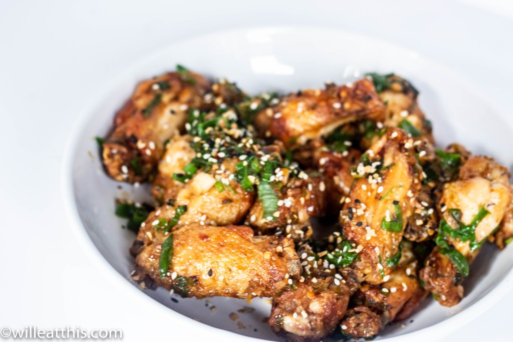 Fried Salt and Pepper Chicken WIngs in a bowl, dusted with specks of sesame seeds and spring onions