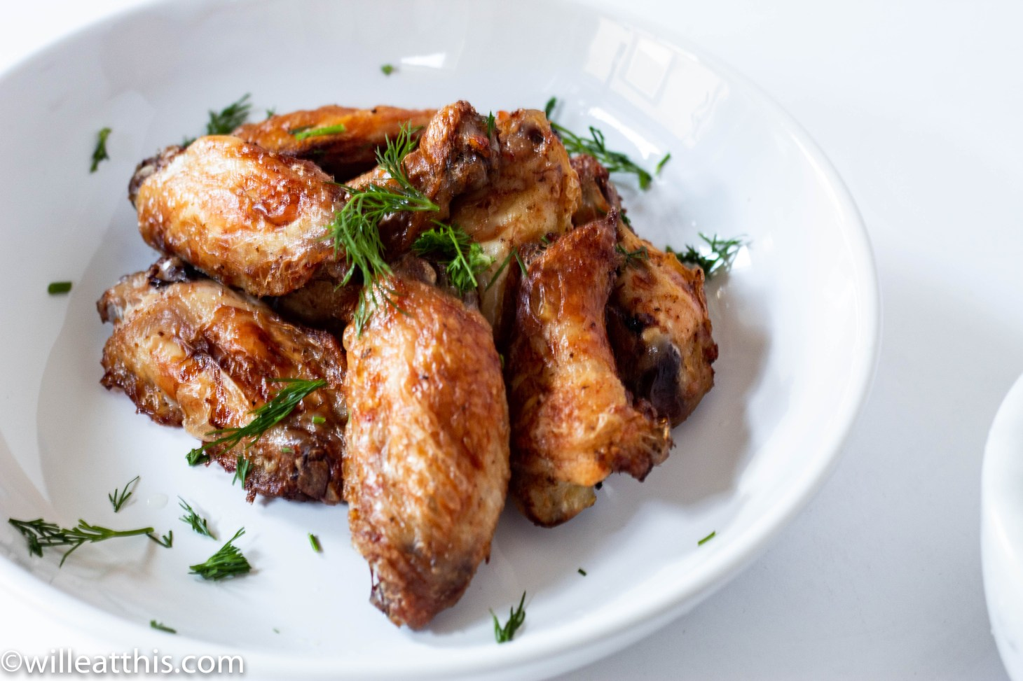 A stack of dill pickle chicken wings in a white plate dusted with chopped dill