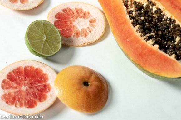 half papaya and slices of limes and grapefruit