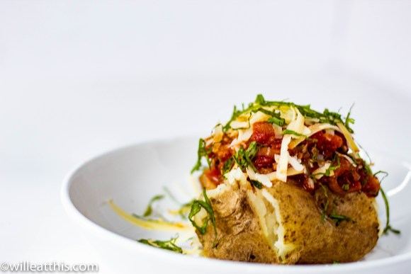 Baked potato topped with tomato eggplant sauce, basil, and cheese on a white plate