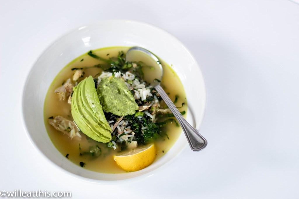 Rice and Kale Chicken Soup with Pesto topped with avocado slices in a white plate