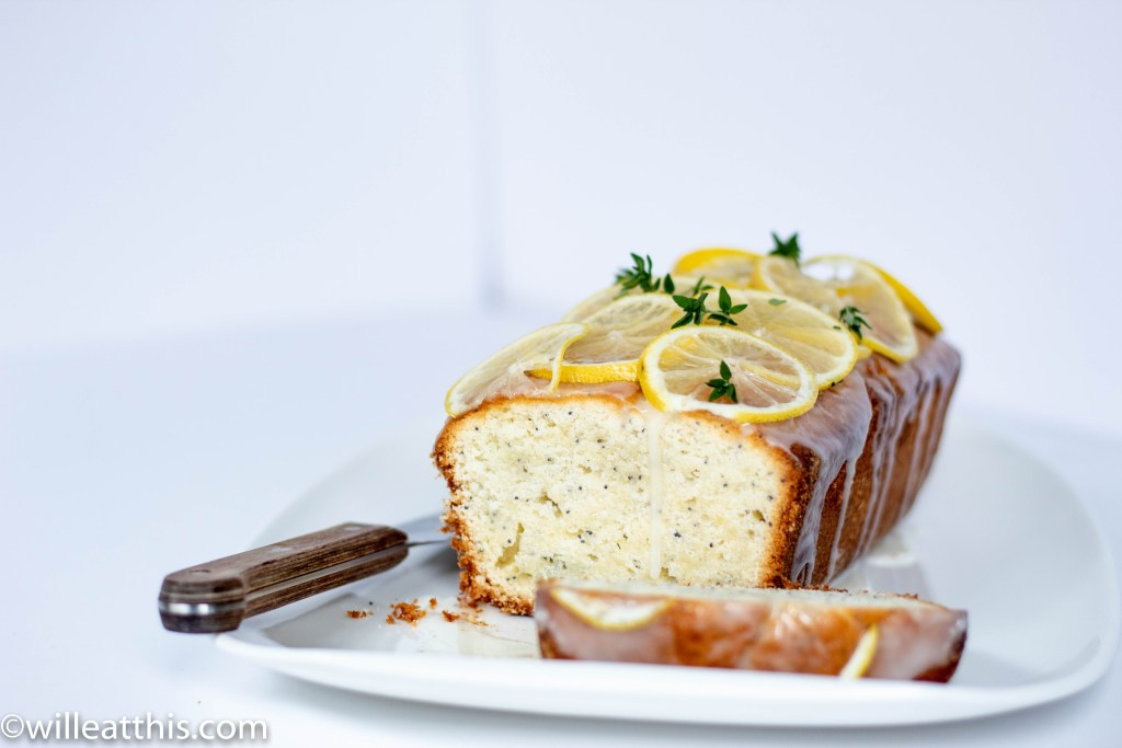 A cut loaf of lemon poppy seed cake decorated with slices of lemon and thyme buds with dripping frosting on a white plate