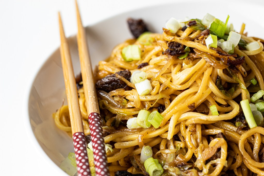 A bowl of lo mein noodles with chunks of soy glazed beef ribs, spring onions and vegetables. There is a pair of chopsticks on the edge of the plate.
