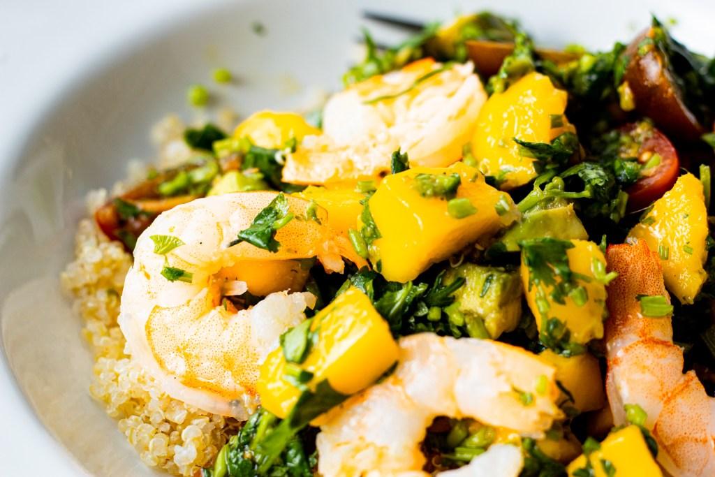 Mango salad with tomato and avocado served with quinoa and shrimp.