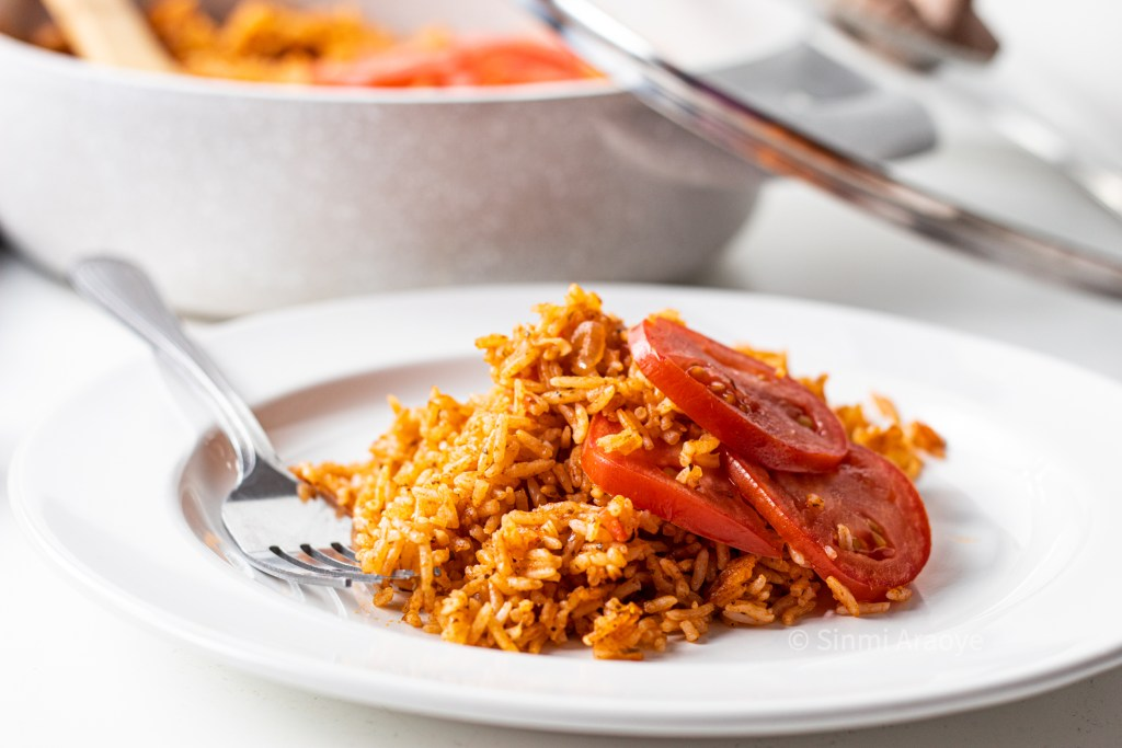 A white plate filled with Nigerian Jollof Rice topped with slices of fresh slices of tomato