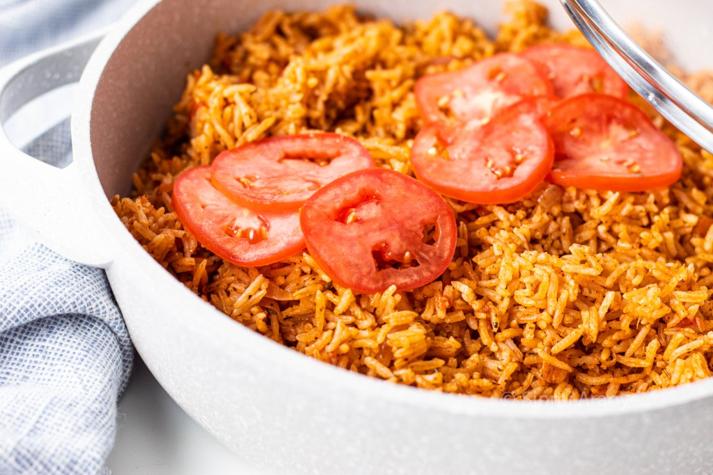 A pot filled with nigerian  jollof rice and topped with slices of tomato