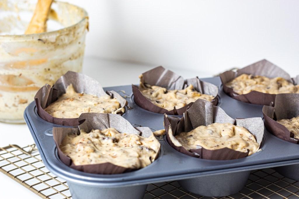 Raw buttermilk banana bread batter in jumbo muffin tin