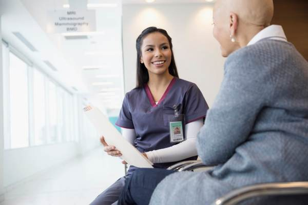 Female nurse discussing medical chart with bald cancer patient in waiting room